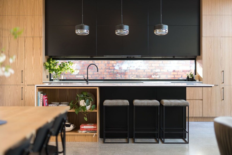 Modern galley kitchen pantry in Melbourne with a drop-in sink, recessed-panel cabinets, black cabinets, quartz benchtops, glass sheet splashback, black appliances, concrete floors and an island.