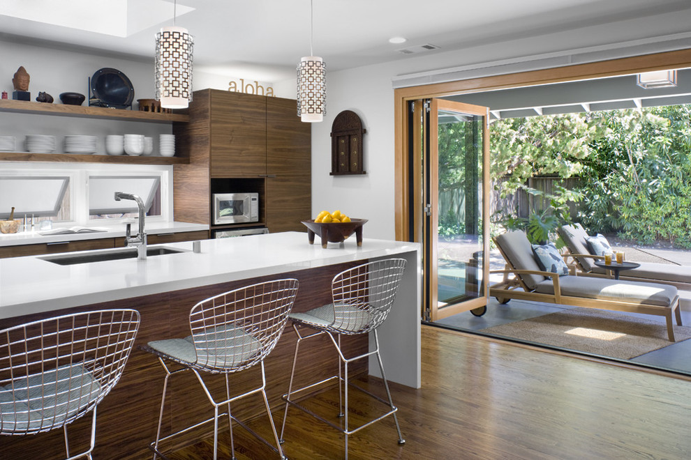Example of a minimalist single-wall medium tone wood floor and brown floor eat-in kitchen design in San Francisco with flat-panel cabinets, medium tone wood cabinets, an island, quartz countertops and stainless steel appliances