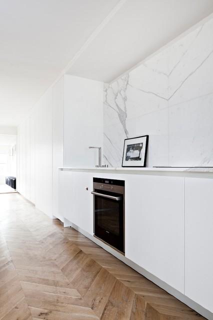 Kitchen With Marble Backsplash And Herringbone Wood Floor