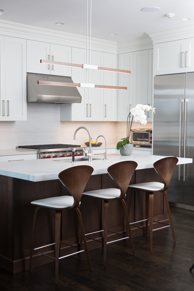 Kitchen - transitional l-shaped dark wood floor kitchen idea in New York with shaker cabinets, white cabinets, white backsplash, stainless steel appliances, an island and marble countertops