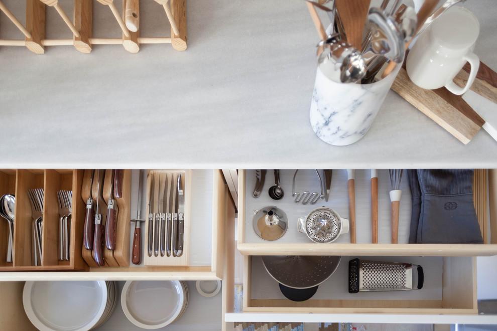 Mid-sized minimalist u-shaped kitchen photo in San Francisco with white cabinets, marble countertops, white backsplash, ceramic backsplash, stainless steel appliances and no island