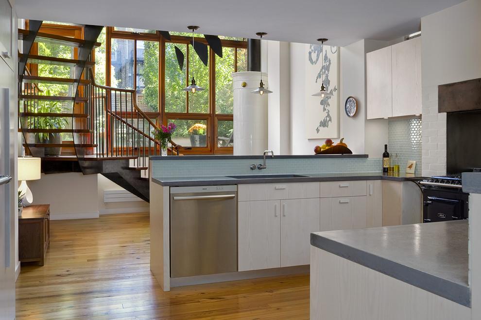 Minimalist kitchen photo in New York with glass tile backsplash, an undermount sink, concrete countertops, black appliances, flat-panel cabinets and blue backsplash