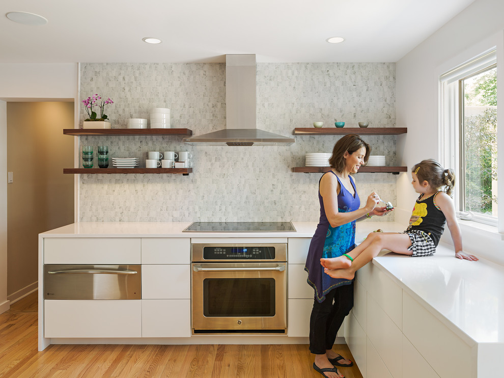 Kitchen - contemporary l-shaped medium tone wood floor kitchen idea in Philadelphia with flat-panel cabinets, white cabinets, multicolored backsplash, stainless steel appliances and no island