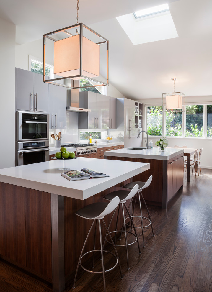 Large trendy galley dark wood floor kitchen photo in San Francisco with an undermount sink, flat-panel cabinets, medium tone wood cabinets, quartz countertops, white backsplash, stainless steel appliances, two islands and glass sheet backsplash