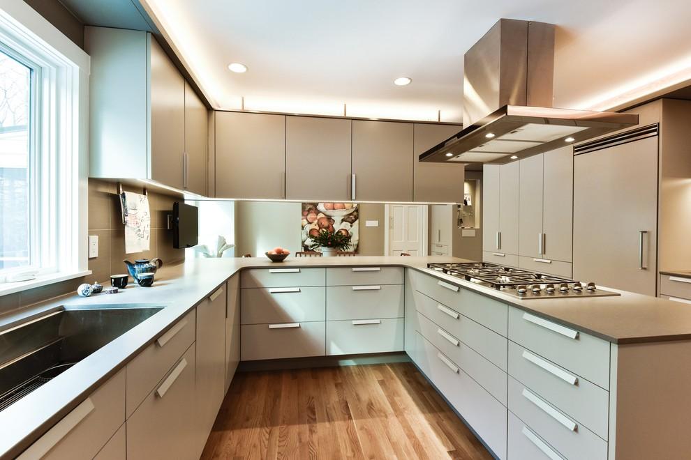 Mid-sized minimalist u-shaped medium tone wood floor eat-in kitchen photo in DC Metro with a farmhouse sink, flat-panel cabinets, gray cabinets, quartz countertops, gray backsplash, porcelain backsplash, paneled appliances and a peninsula