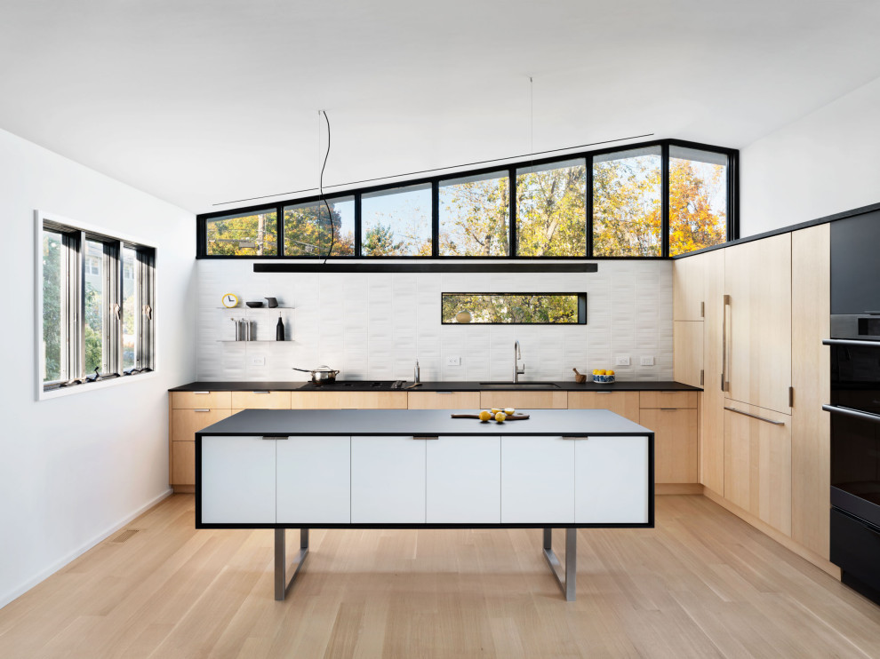 Trendy light wood floor and vaulted ceiling kitchen photo in New York with an undermount sink, flat-panel cabinets, light wood cabinets, laminate countertops, white backsplash, ceramic backsplash, black appliances, an island and black countertops