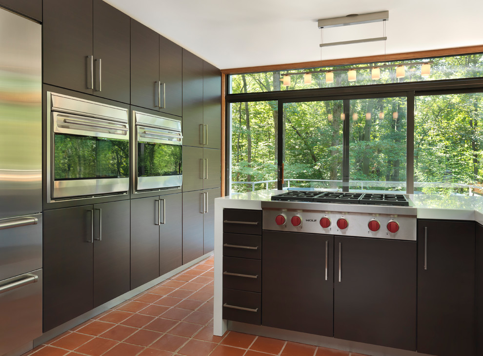 Enclosed kitchen - mid-sized modern l-shaped terra-cotta tile enclosed kitchen idea in Providence with stainless steel appliances, an undermount sink, flat-panel cabinets, dark wood cabinets, quartz countertops and no island