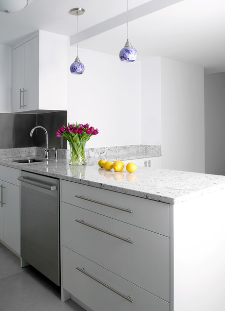 Example of a mid-sized minimalist l-shaped slate floor open concept kitchen design in New York with an undermount sink, white cabinets, stainless steel appliances, an island, shaker cabinets, quartz countertops, white backsplash and matchstick tile backsplash