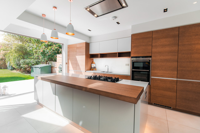 This is an example of a medium sized contemporary galley kitchen/diner in London with a single-bowl sink, flat-panel cabinets, medium wood cabinets, quartz worktops, white splashback, stainless steel appliances, an island, white worktops and white floors.