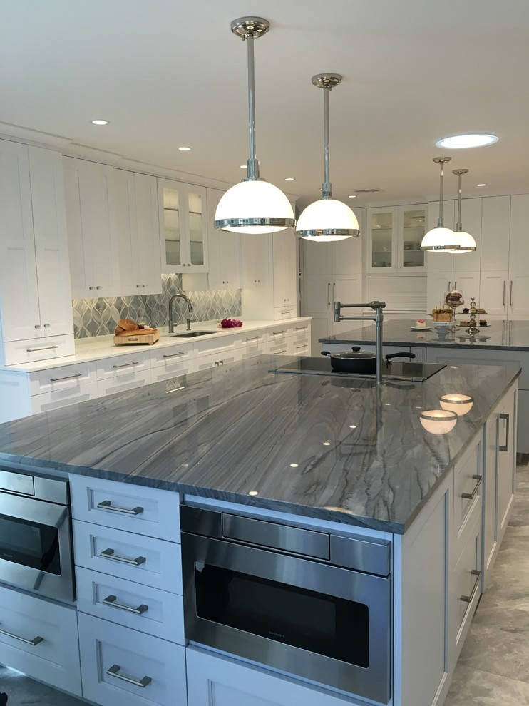 Inspiration for a huge contemporary u-shaped ceramic tile eat-in kitchen remodel in New York with a single-bowl sink, shaker cabinets, white cabinets, quartzite countertops, gray backsplash, glass sheet backsplash, stainless steel appliances and two islands