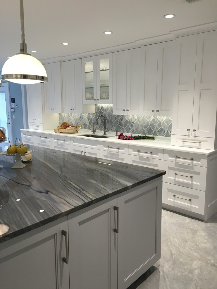 Huge trendy u-shaped ceramic tile eat-in kitchen photo in New York with a single-bowl sink, shaker cabinets, white cabinets, quartzite countertops, gray backsplash, glass sheet backsplash, stainless steel appliances and two islands