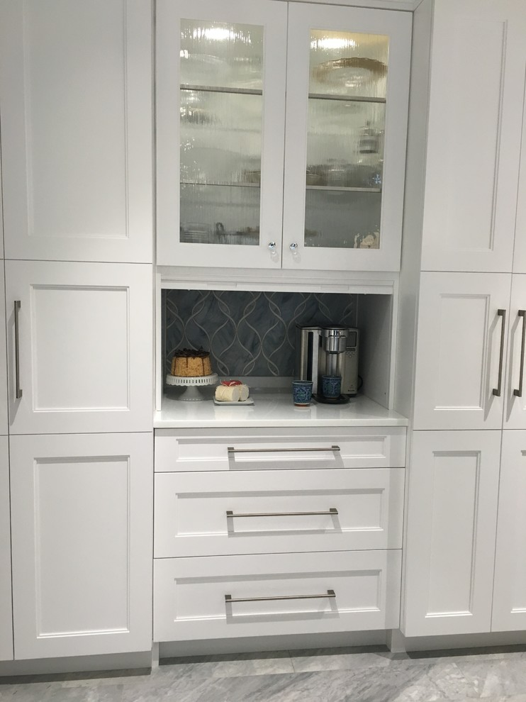 Eat-in kitchen - huge contemporary u-shaped ceramic tile eat-in kitchen idea in New York with a single-bowl sink, shaker cabinets, white cabinets, quartzite countertops, gray backsplash, glass sheet backsplash, stainless steel appliances and two islands