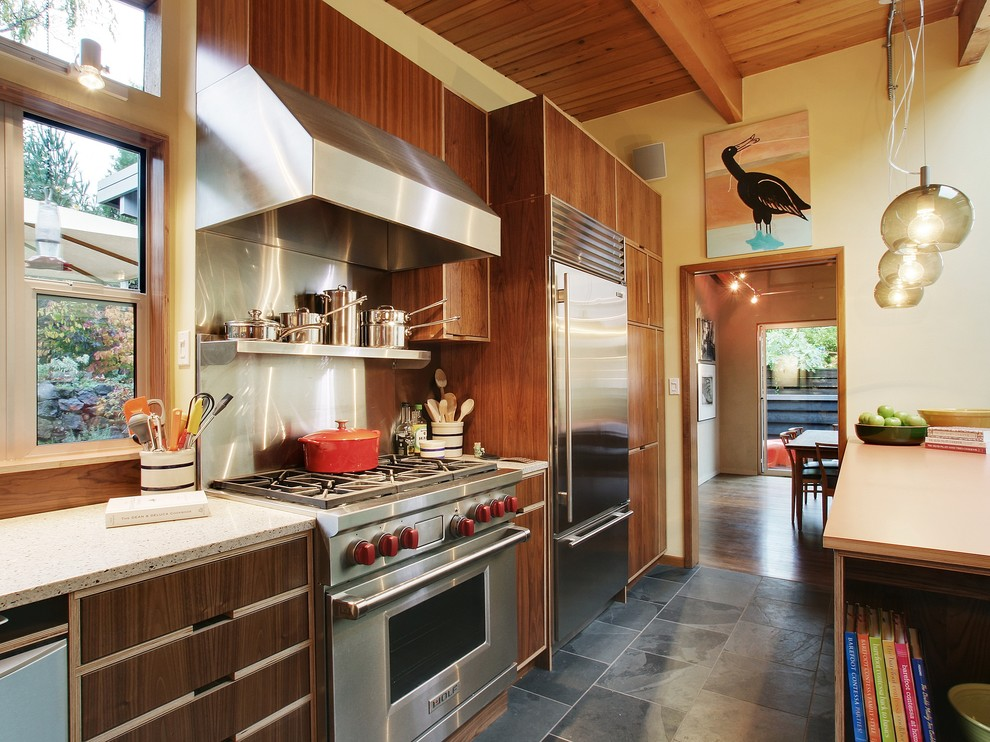 Kitchen - mid-sized modern slate floor and black floor kitchen idea in Seattle with flat-panel cabinets, stainless steel appliances, metallic backsplash, metal backsplash, dark wood cabinets and granite countertops