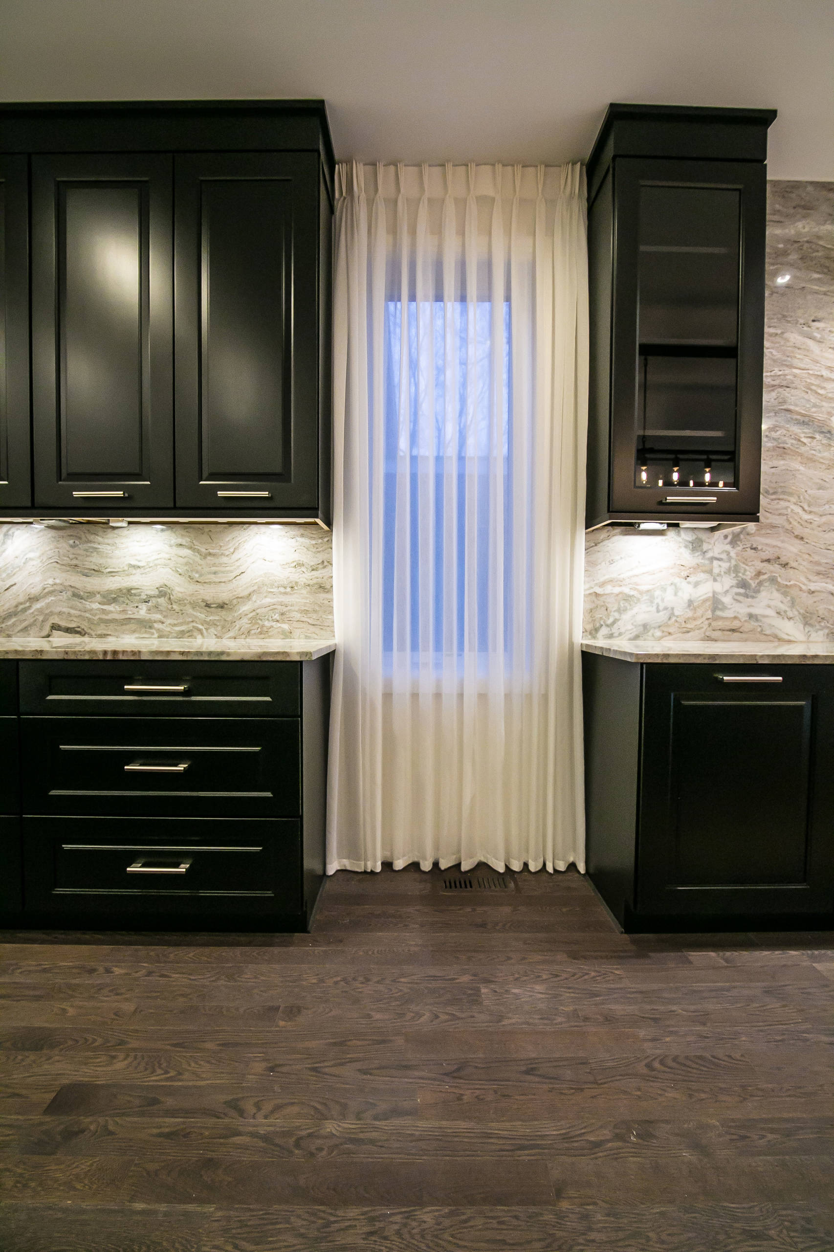 The desire for a modern, yet luxurious, aesthetic inspired a specific attention to detail and material for this home in Huntington Woods. Custom black cabinetry, Fantasy Brown quartzite and stainless