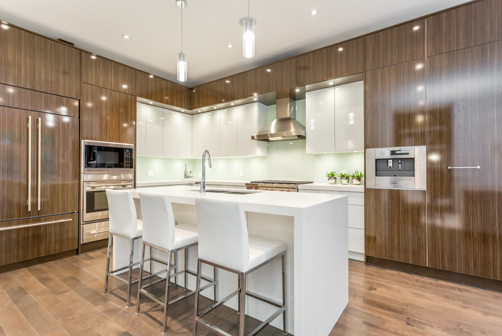 Example of a large trendy l-shaped light wood floor and brown floor enclosed kitchen design in Toronto with a double-bowl sink, flat-panel cabinets, white backsplash, glass sheet backsplash, paneled appliances, an island, dark wood cabinets and quartz countertops