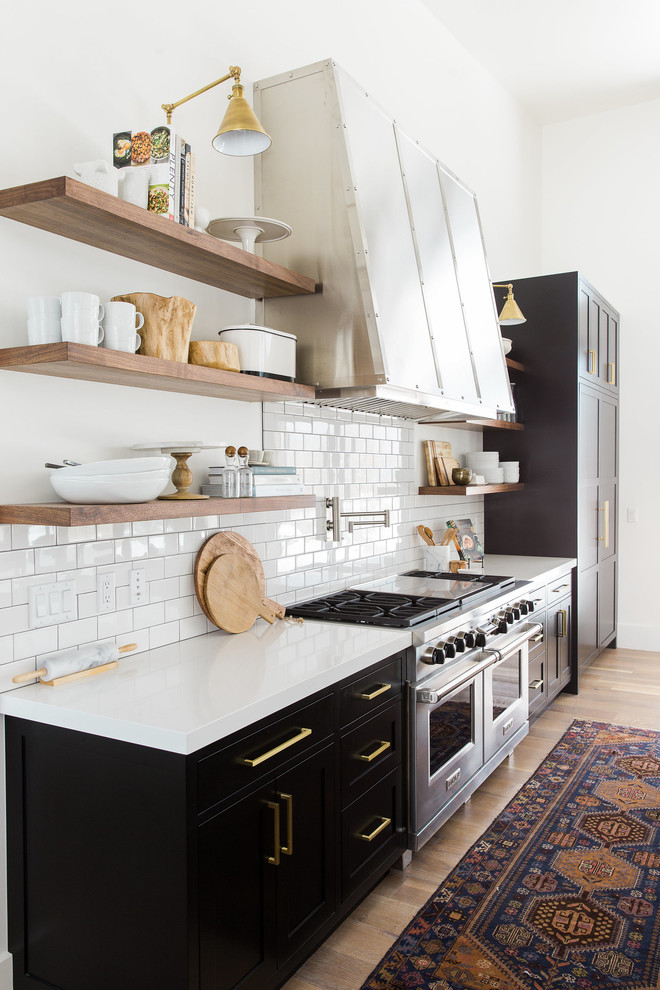 Open concept kitchen - transitional single-wall light wood floor open concept kitchen idea in Salt Lake City with a drop-in sink, flat-panel cabinets, black cabinets, white backsplash, subway tile backsplash, stainless steel appliances and an island