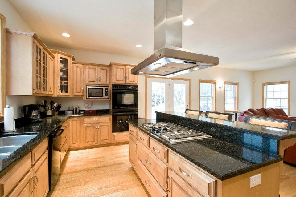 Open concept kitchen - large transitional l-shaped light wood floor open concept kitchen idea in Other with a double-bowl sink, raised-panel cabinets, light wood cabinets, granite countertops, stainless steel appliances and an island