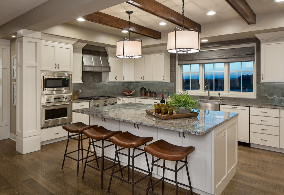 Foto de cocinas en L gris y blanca, tradicional renovada, con fregadero sobremueble, armarios estilo shaker, puertas de armario blancas, salpicadero verde, electrodomésticos de acero inoxidable, suelo de madera oscura y una isla