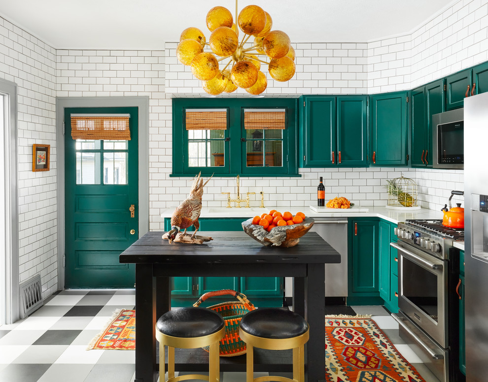 Example of an eclectic l-shaped kitchen design in Chicago with shaker cabinets, blue cabinets, white backsplash, subway tile backsplash, stainless steel appliances, an island and white countertops