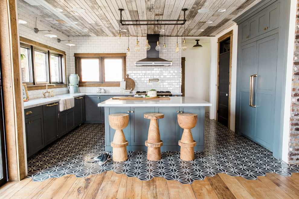 Example of an urban u-shaped cement tile floor and multicolored floor kitchen design in Salt Lake City with shaker cabinets, blue cabinets, white backsplash, subway tile backsplash, paneled appliances, an island and white countertops