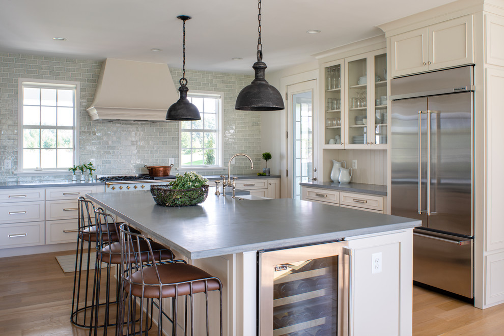Example of a large farmhouse light wood floor and beige floor eat-in kitchen design in DC Metro with a farmhouse sink, concrete countertops, blue backsplash, glass tile backsplash, an island, gray countertops, recessed-panel cabinets, beige cabinets and stainless steel appliances