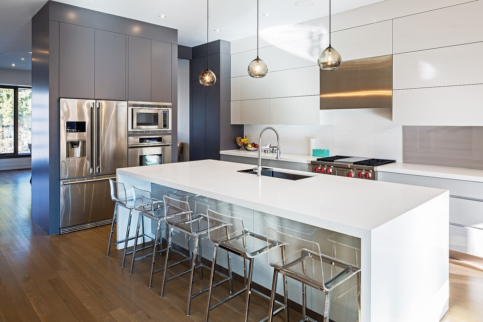 Example of a large minimalist l-shaped medium tone wood floor and brown floor open concept kitchen design in Toronto with an undermount sink, flat-panel cabinets, white cabinets, white backsplash, stainless steel appliances, an island, solid surface countertops and glass sheet backsplash