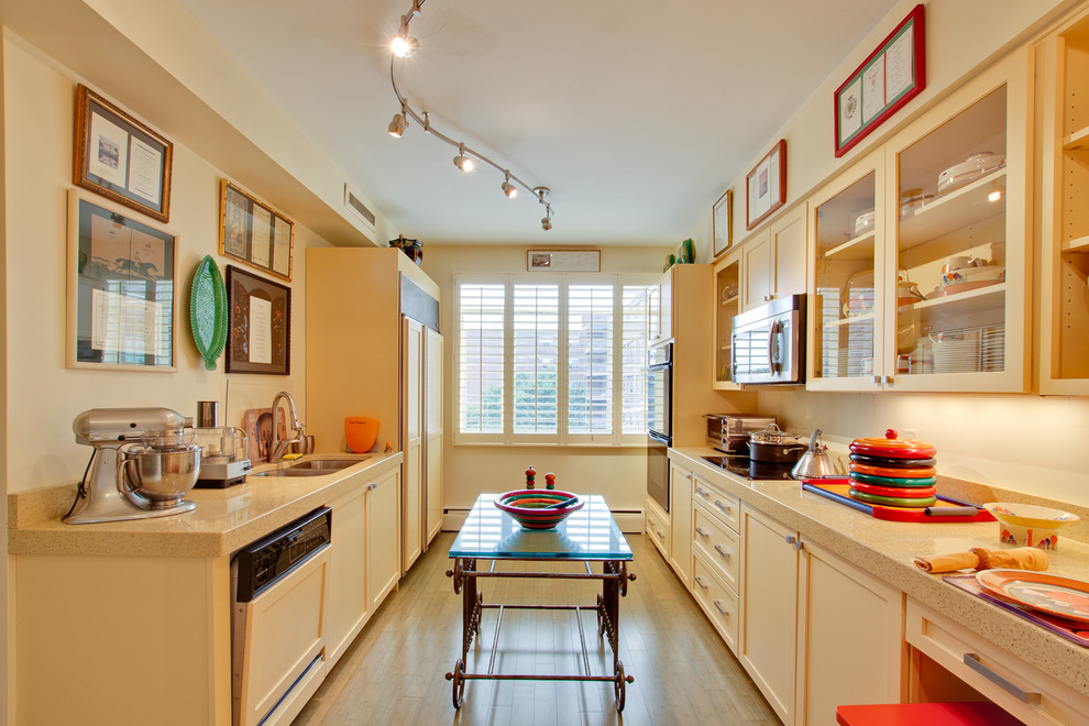 Example of an eclectic galley enclosed kitchen design in DC Metro with shaker cabinets, a double-bowl sink, yellow cabinets and paneled appliances