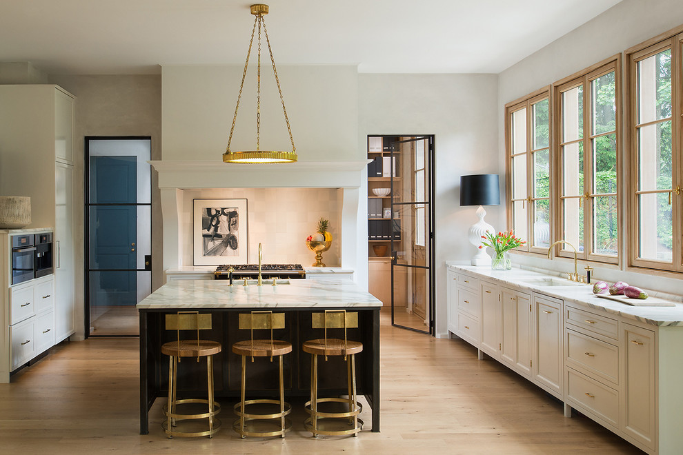 Transitional u-shaped light wood floor enclosed kitchen photo in DC Metro with an undermount sink, recessed-panel cabinets, white cabinets, marble countertops and an island
