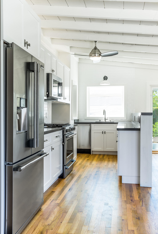 Small transitional u-shaped medium tone wood floor and brown floor kitchen photo in Orange County with an undermount sink, shaker cabinets, white cabinets, quartzite countertops, white backsplash, ceramic backsplash, stainless steel appliances and no island