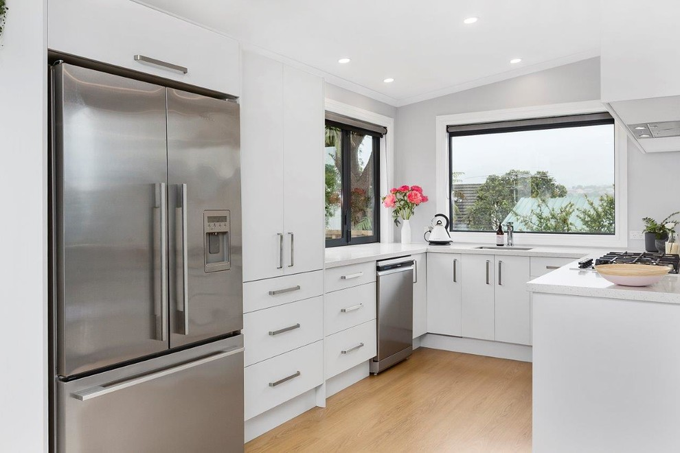Scandinavian u-shaped kitchen with a drop-in sink, white cabinets, white splashback, ceramic splashback, stainless steel appliances, laminate floors and brown floor.