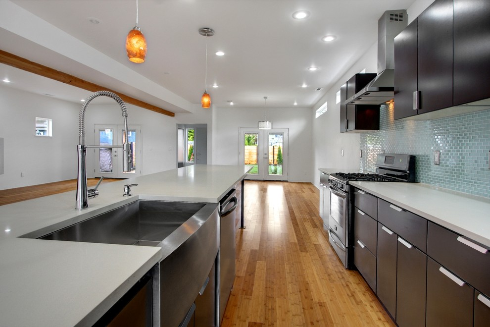 Large minimalist galley medium tone wood floor eat-in kitchen photo in Seattle with a farmhouse sink, flat-panel cabinets, dark wood cabinets, blue backsplash, mosaic tile backsplash, stainless steel appliances and a peninsula