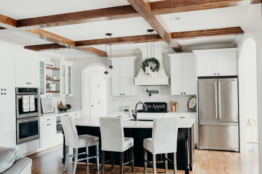 Inspiration for a large farmhouse l-shaped medium tone wood floor and brown floor eat-in kitchen remodel in Charlotte with an undermount sink, recessed-panel cabinets, white cabinets, quartz countertops, white backsplash, stone tile backsplash, stainless steel appliances, an island and white countertops