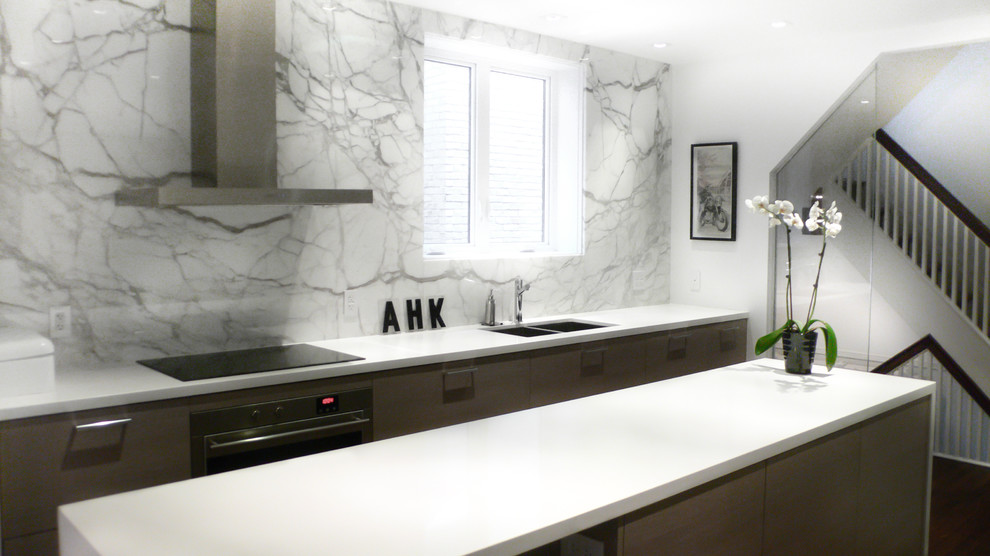Inspiration for a mid-sized contemporary l-shaped medium tone wood floor and brown floor open concept kitchen remodel in Toronto with a double-bowl sink, quartz countertops, white backsplash, flat-panel cabinets, gray cabinets, stone slab backsplash, paneled appliances and an island