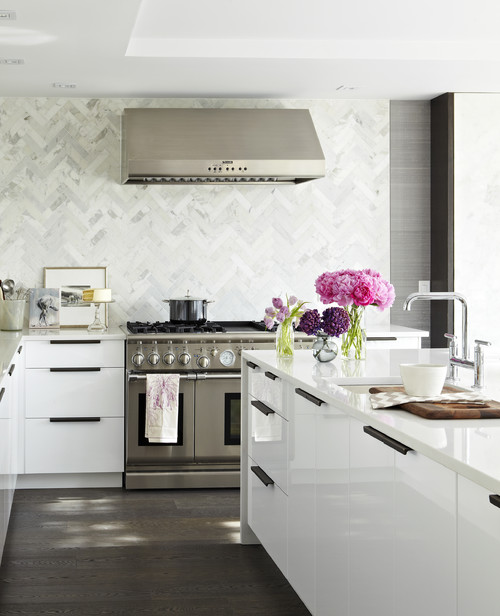 In this modern kitchen design, a tightly woven, herringbone pattern is created with a subway tile filling the entire wall.