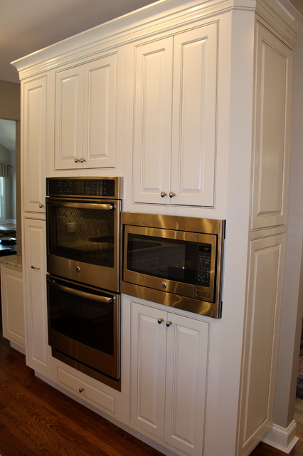 Inspiration for a mid-sized modern l-shaped eat-in kitchen remodel in Cincinnati with an undermount sink, raised-panel cabinets, white cabinets, granite countertops, multicolored backsplash, mosaic tile backsplash, stainless steel appliances and an island