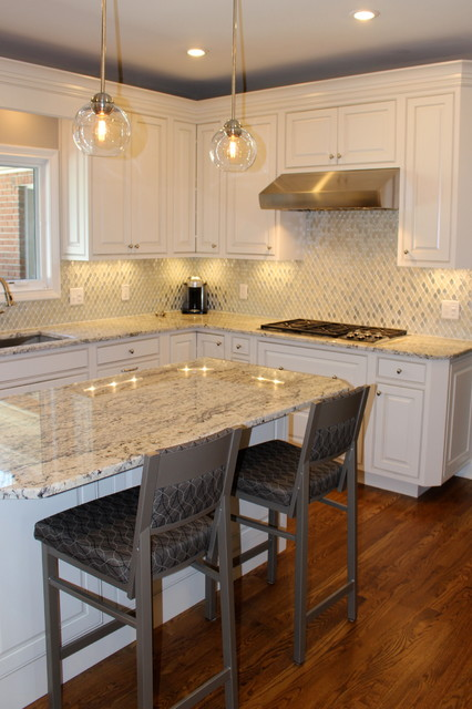 Mid-sized minimalist l-shaped eat-in kitchen photo in Cincinnati with an undermount sink, raised-panel cabinets, white cabinets, granite countertops, multicolored backsplash, mosaic tile backsplash, stainless steel appliances and an island