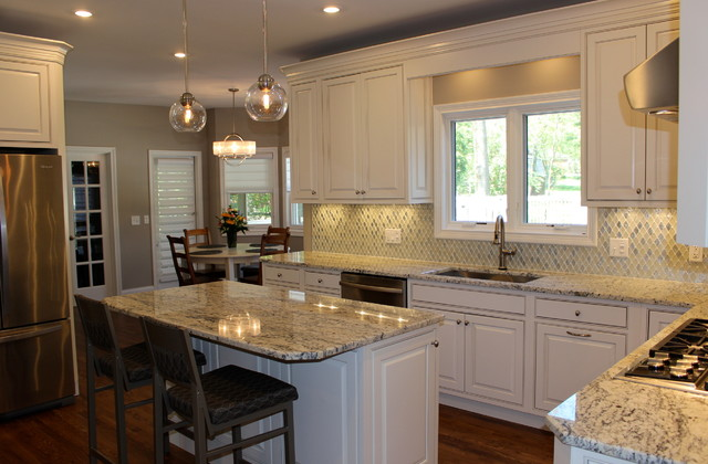 Example of a mid-sized minimalist l-shaped dark wood floor enclosed kitchen design in Cincinnati with an undermount sink, shaker cabinets, white cabinets, granite countertops, multicolored backsplash, mosaic tile backsplash, stainless steel appliances and an island