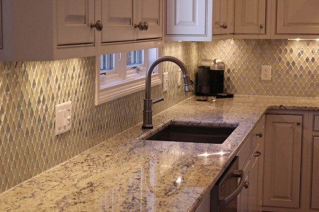 Eat-in kitchen - mid-sized modern l-shaped eat-in kitchen idea in Cincinnati with an undermount sink, raised-panel cabinets, white cabinets, granite countertops, multicolored backsplash, mosaic tile backsplash, stainless steel appliances and an island