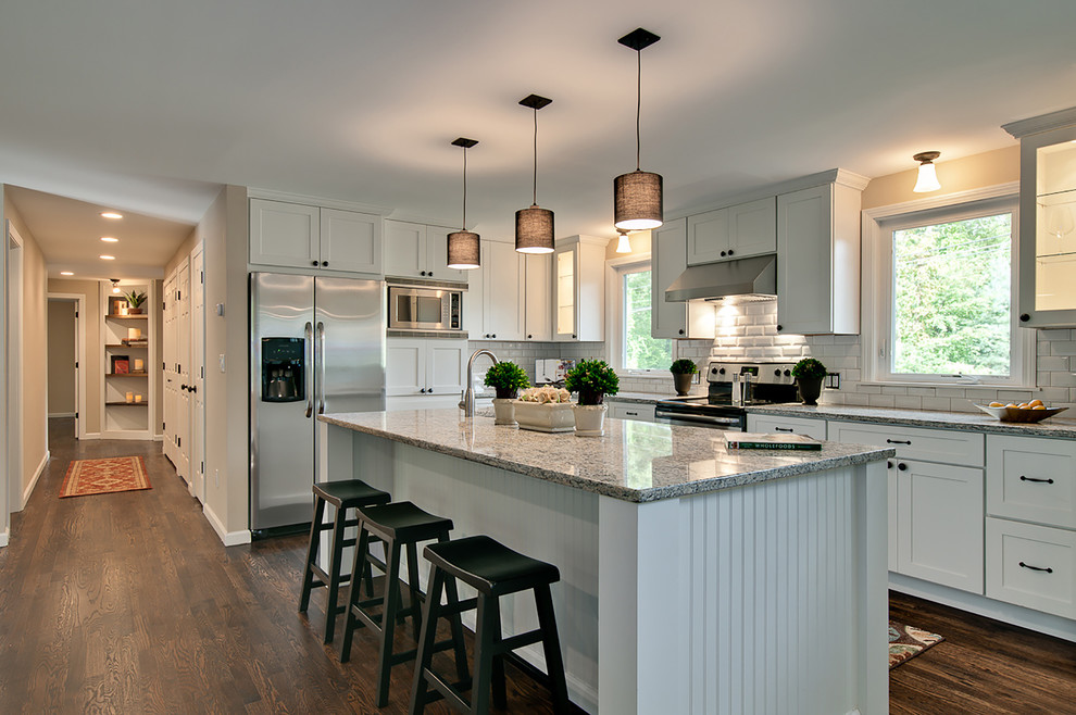 Example of a mid-sized transitional medium tone wood floor eat-in kitchen design in Minneapolis with shaker cabinets, white cabinets, stainless steel appliances and an island