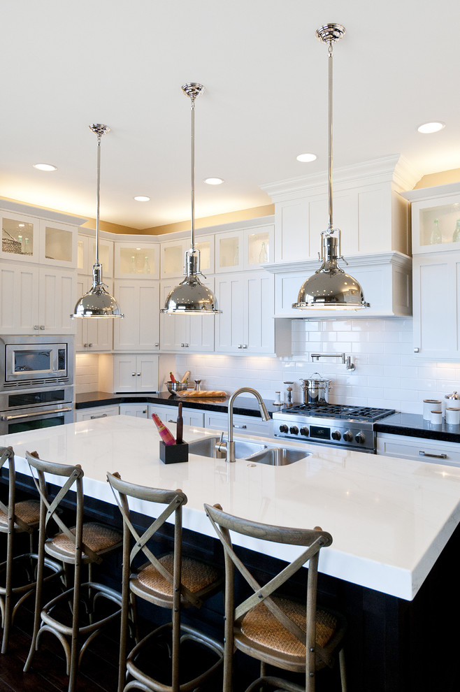 Kitchen - large traditional l-shaped kitchen idea in Salt Lake City with stainless steel appliances, subway tile backsplash, an undermount sink, shaker cabinets, dark wood cabinets, marble countertops, white backsplash and an island