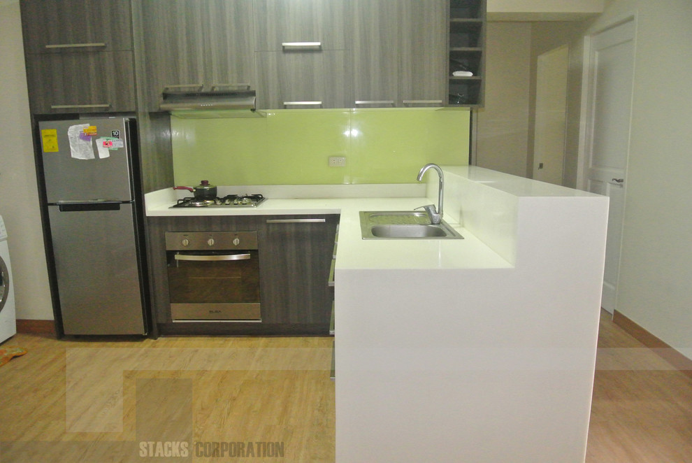 Example of a mid-sized minimalist l-shaped kitchen pantry design in Other with solid surface countertops, stainless steel appliances and no island