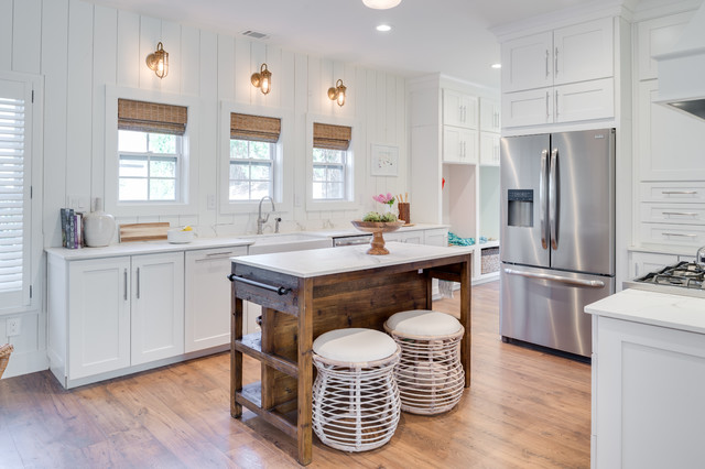 Inspiration for a cottage medium tone wood floor and beige floor enclosed kitchen remodel in Orange County with a farmhouse sink, shaker cabinets, white cabinets, stainless steel appliances, quartz countertops and an island