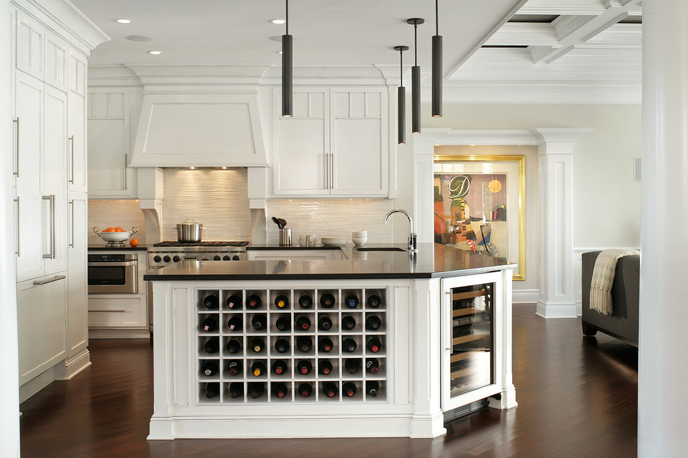 Example of a classic open concept kitchen design in Miami with recessed-panel cabinets, white cabinets, beige backsplash and paneled appliances