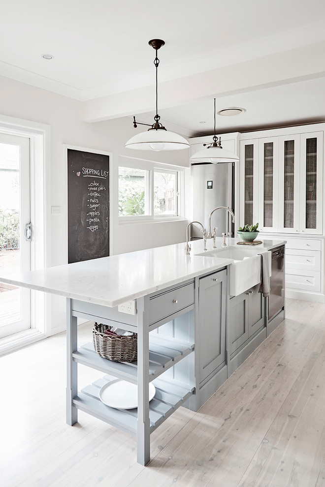 Example of a mid-sized country light wood floor and gray floor kitchen design in Sydney with a farmhouse sink, shaker cabinets, marble countertops, stainless steel appliances, an island and gray cabinets