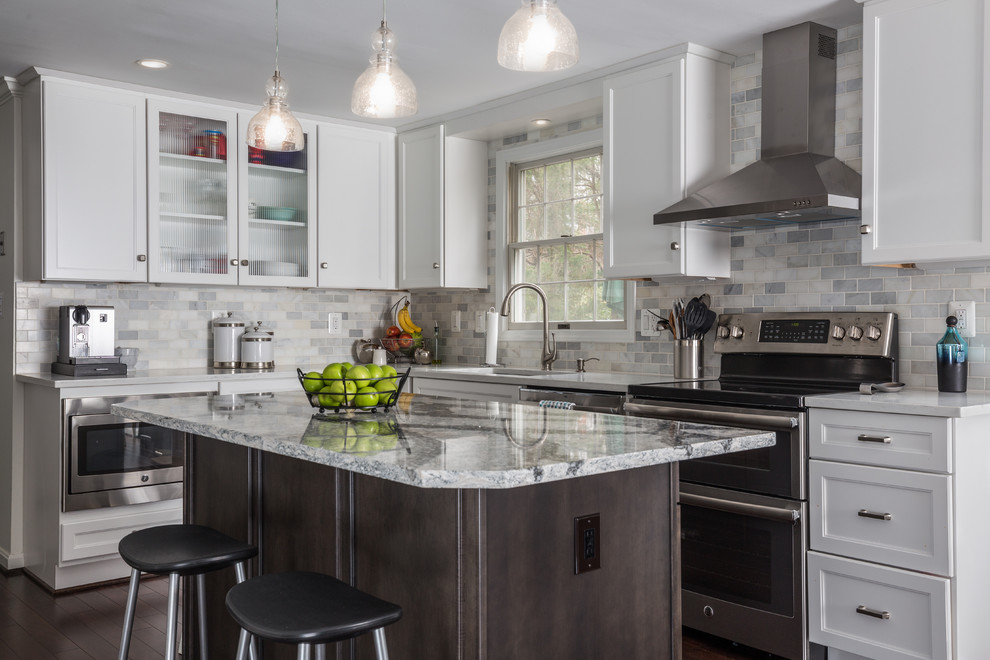 Example of a mid-sized transitional l-shaped dark wood floor and brown floor eat-in kitchen design in DC Metro with an undermount sink, shaker cabinets, white cabinets, quartz countertops, white backsplash, stone tile backsplash, stainless steel appliances and an island