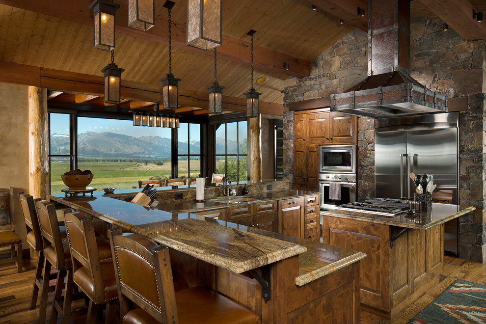 Large mountain style u-shaped medium tone wood floor and brown floor eat-in kitchen photo in Other with an undermount sink, raised-panel cabinets, medium tone wood cabinets, stainless steel appliances, granite countertops, an island, multicolored backsplash and stone tile backsplash