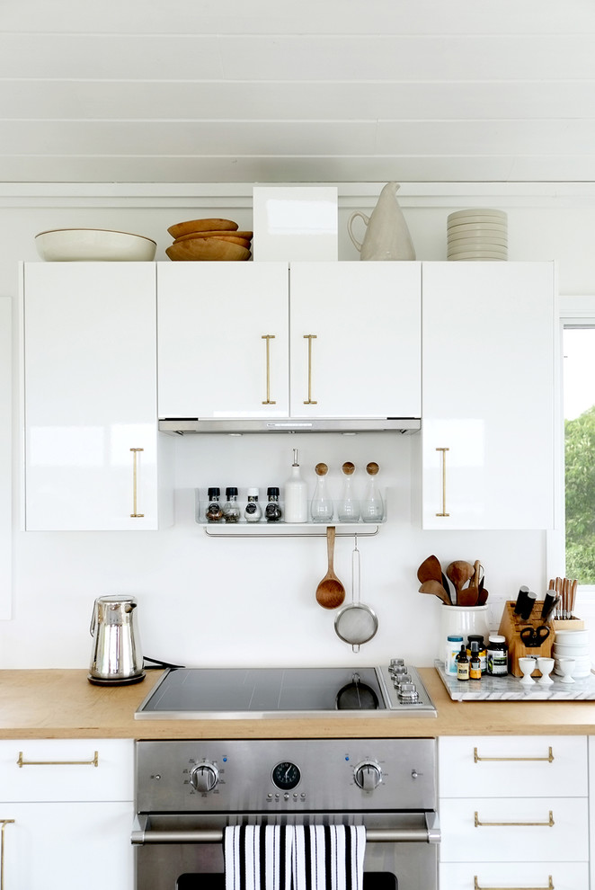 Photo of a contemporary kitchen in New York with flat-panel cabinets, white cabinets, white splashback, stainless steel appliances and wood worktops.