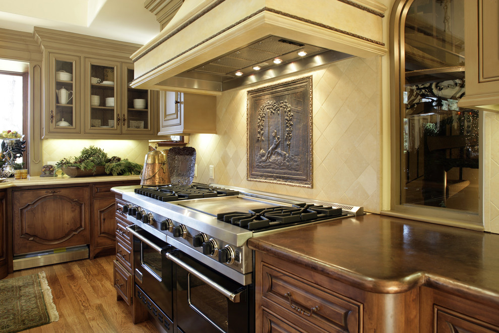 Inspiration for a mediterranean kitchen remodel in San Francisco with copper countertops, dark wood cabinets, beige backsplash, black appliances and limestone backsplash