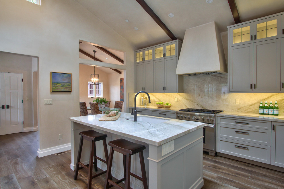 Inspiration for a large transitional l-shaped dark wood floor and brown floor open concept kitchen remodel in Other with an undermount sink, shaker cabinets, gray cabinets, marble countertops, beige backsplash, marble backsplash, stainless steel appliances and an island