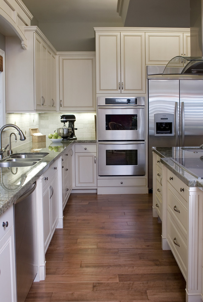 Example of a classic kitchen design in Los Angeles with stainless steel appliances, a triple-bowl sink, raised-panel cabinets, white cabinets, white backsplash and granite countertops